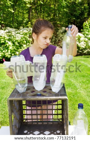 Young girl works on her Science Fair project - making a face as she checks  temperature - stock photo