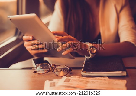 young girl works on the tablet on the internet and goes to the train - stock photo