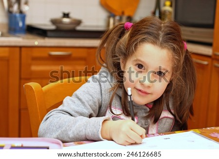 young girl writes on the notebook of schoolwork - stock photo