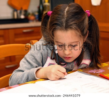 young  girl writes with pencil on notebook exercises