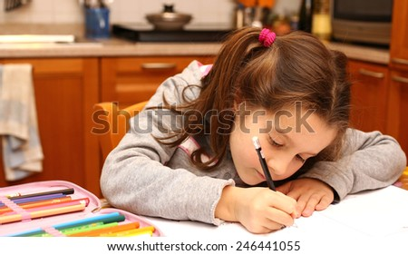 young girl writes with pencil on the school book in the kitchen - stock photo
