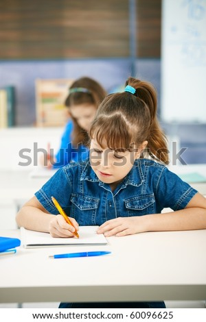 Young girl writing at school sitting in class with other girl in background.? - stock photo