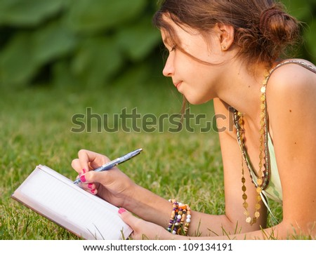 Young girl writing into her notebook in the park