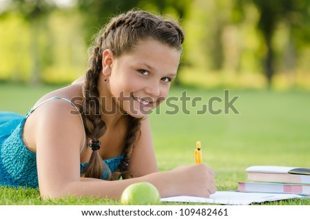 Young girl writing into her notebook in the park - stock photo