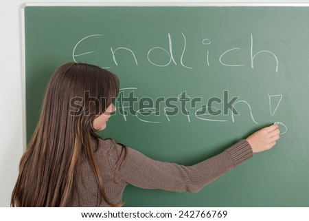 Young girl writing on blackboard finally holidays - stock photo