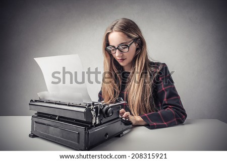 young girl writing something with a typewriter - stock photo