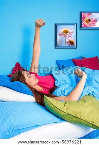 young girl yawing in bed before standing up - stock photo