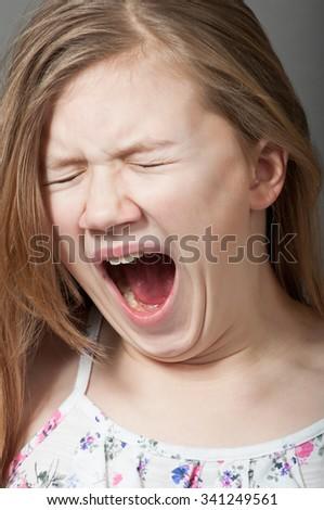 Young girl yawning - stock photo