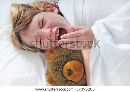 young girl yawning in bed with bear - stock photo