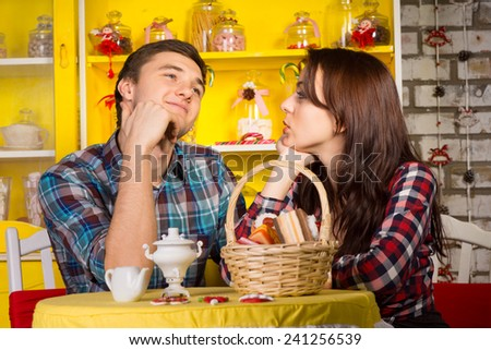 Young Girlfriend Looking at her Smiling Thoughtful Boyfriend While Having a Date at the Cafe Shop. - stock photo