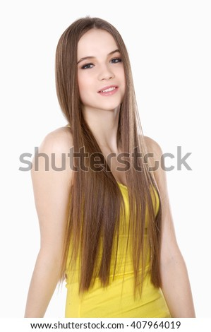 Young girlin yellow dress  with long straight hair posing on white background - stock photo