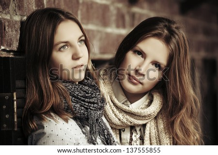 Young girls against a brick wall - stock photo