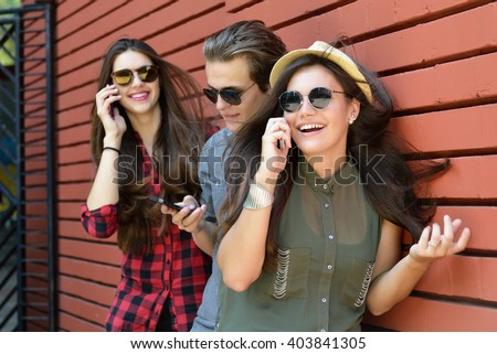 Young girls and boy having fun outdoor and using smart phone against red brick wall. Urban lifestyle, happiness, joy, friends, social network concept. Image toned and noise added. - stock photo