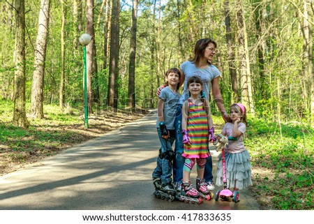 young girls and boy in protective equipment and rollers scating with mother in park, family outdoor portrait - stock photo