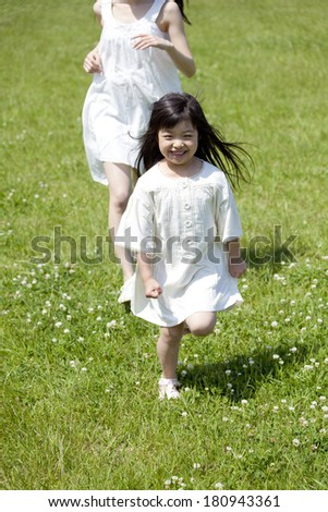 Young girls and Japanese woman running the prairie