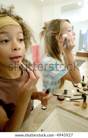 Young girls applying make up - stock photo