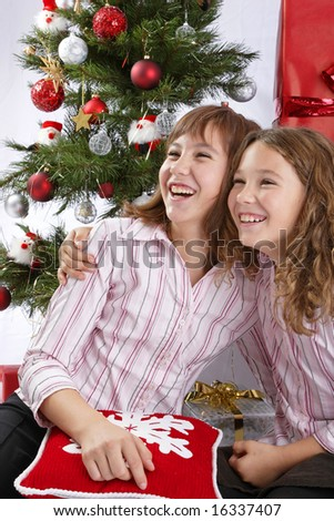 young girls are celebrating christmas in front of a christmas tree