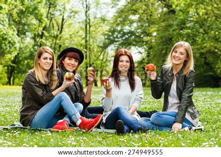 Young girls are sitting in the park and holding apple.Healthy snack for young girls