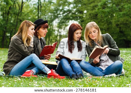 Young girls are surprised because of something they had read in a book.Surprised students