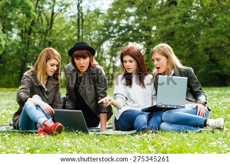 Young girls are very surprised because of something they saw on their laptop.Surprised girls - stock photo