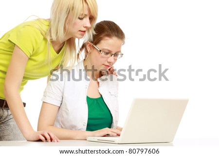 Young girls are working on a laptop - on white background - stock photo