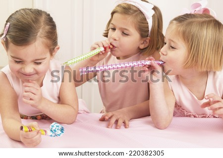 Young girls blowing party favors at their friend