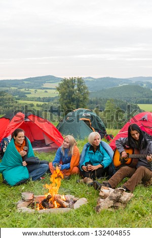 Young girls camping with tents beside campfire in nature landscape - stock photo