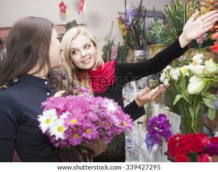 Young girls choose beautiful flowers pot - stock photo