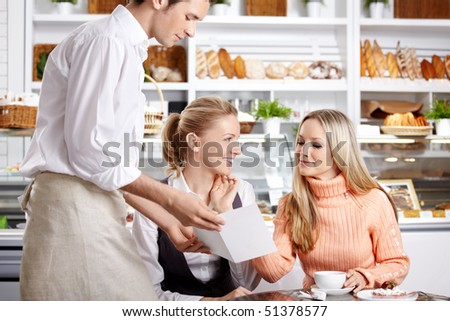 Young girls do the order to the waiter in cafe - stock photo