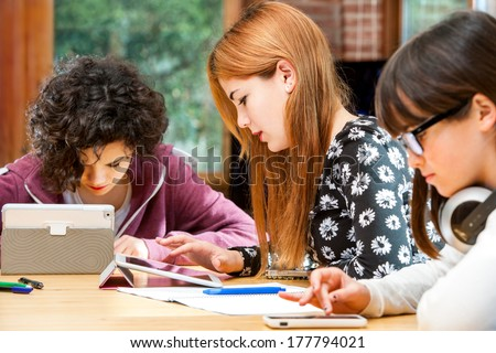Young girls doing homework together at desk with tablets. - stock photo