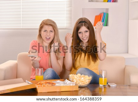 Young girls eating pizza and watching TV