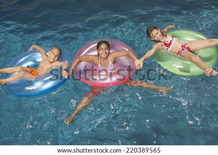 Young girls floating in inner tubes - stock photo