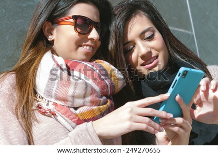Young girls & friends standing using a smartphone - stock photo