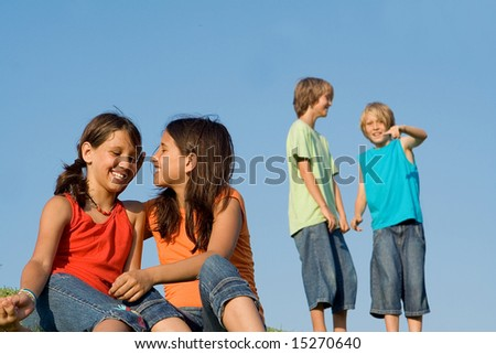 young girls giggling and whispering with boys behind - stock photo