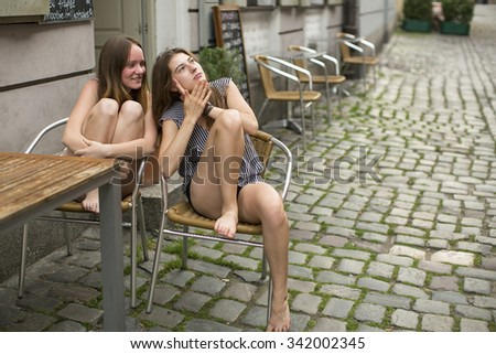 Young girls gossiping while sitting in a street cafe. - stock photo