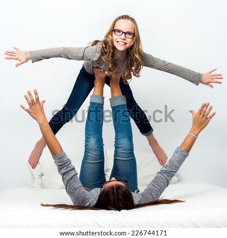 Young girls having fun playing games on bed at home. - stock photo