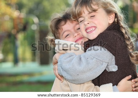 Young girls hugging outside - stock photo