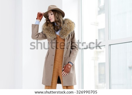 Young girls in coats posing at studio - stock photo
