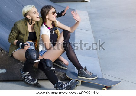 Young girls in skate park with roller skates and skate board  - stock photo