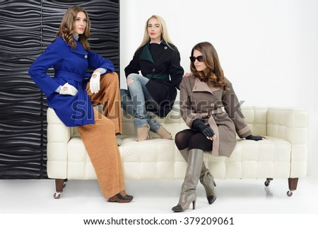 Young girls in studio posing at coats