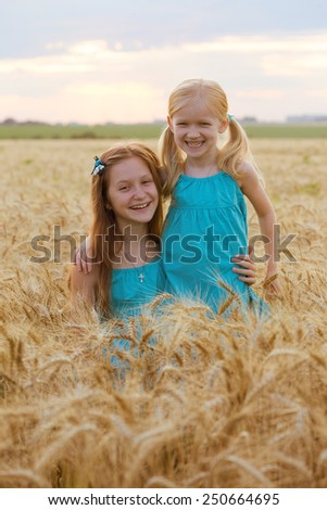 young girls joys on the wheat field   - stock photo