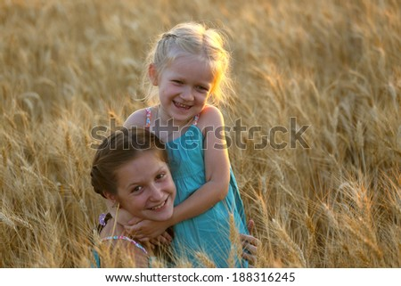 young girls joys on the wheat field at the sunset time