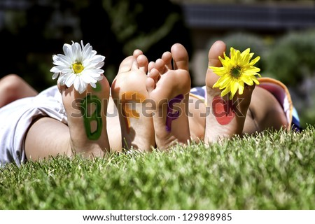 Young girls laying in the grass with daisies in their toes and best friends forever painted on the bottoms of their feet - stock photo