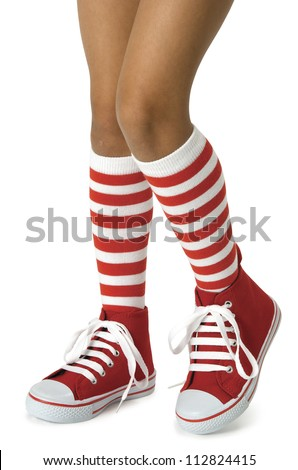 Young girls legs wearing long red striped socks with red shoes on a white background. Clipping path included.