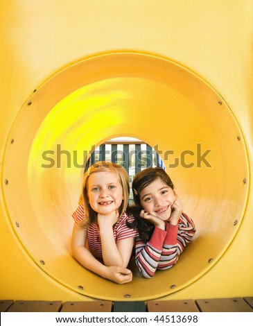 Young girls lying together in crawl tube at playground. Vertically framed shot. - stock photo