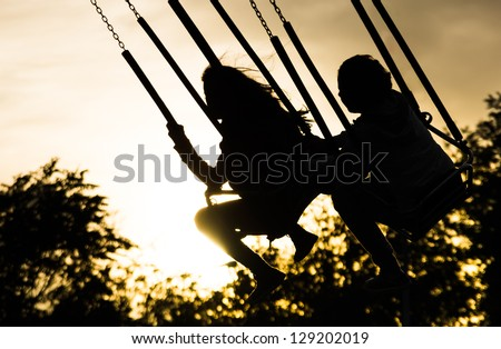 Young girls on Merry Go Round at Sunset - stock photo
