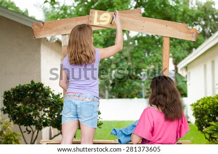 Young girls painting lemonade stand