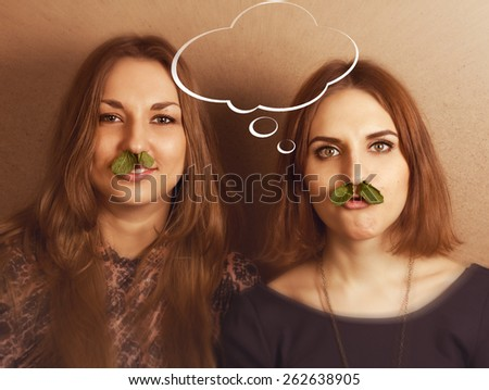 Young girls play the fool with  some idea in empty bubble on brown blurred background. - stock photo