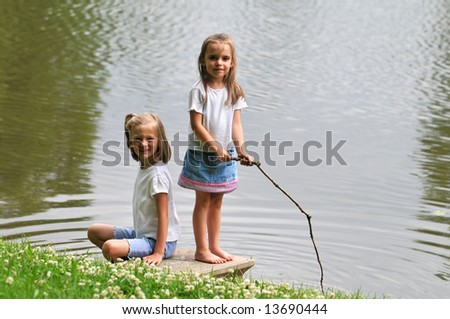 Young girls playing by a lake