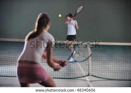 young girls playing tennis game indoori in tennis court - stock photo